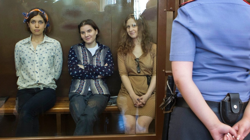 Aug. 3, 2012: Pussy Riot members, from left, Nadezhda Tolokonnikova, Yekaterina Samutsevich and Maria Alekhina sit in a glass cage at a court room  in Moscow, Russia.