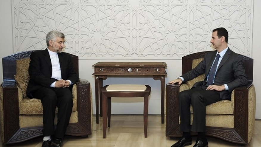 Aug. 7, 2012: In this photo provided by the Syrian official news agency SANA, Syrian President Bashar Assad, right, meets with Saeed Jalili, secretary of Iran's Supreme National Security Council, in Damascus, Syria.