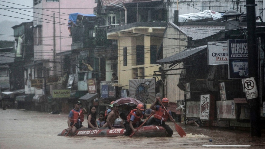 Aug. 7, 2012: Rescuers paddle to higher grounds as they evacuate residents in Marikina, east of Manila, Philippines.