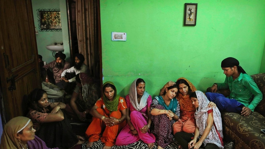Aug. 7, 2012: Indian Lokinder Kaur, third from right, mourns with her daughters Jasbir Kaur, 24, fourth from right, and Jaspreet Kaur, 21, second right, as they gather with other relatives at the family home in New Delhi, India.