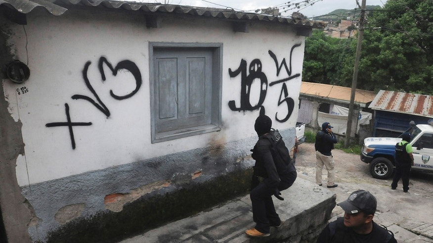 In this June 14, 2012 photo, national police recover a home that had been seized by gangs in the 14 de Marzo neighborhood in Tegucigalpa, Honduras. (AP Photo/Fernando Antonio)