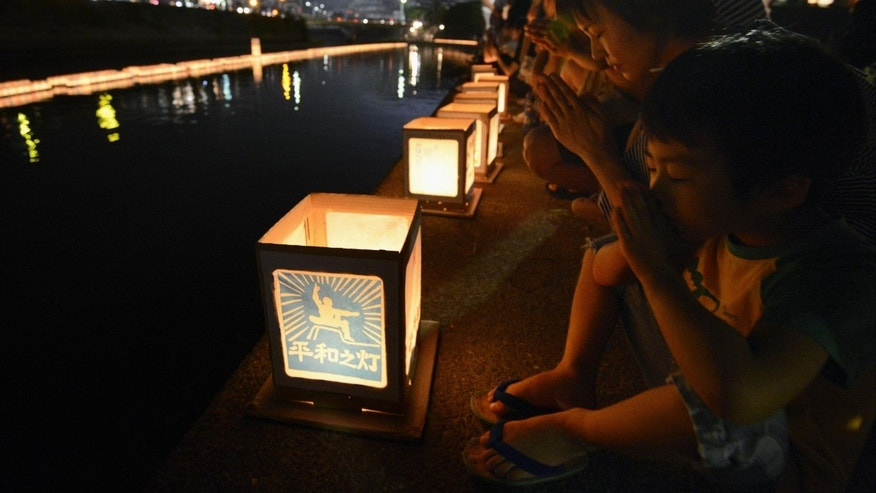 A woman and a boy pray next to lanterns along a river, paying tribute to the victims of the atomic bombing in Nagasaki, southern Japan, Thursday, Aug. 9, 2012. (AP Photo/Kyodo News) JAPAN OUT, MANDATORY CREDIT, NO LICENSING IN CHINA, HONG KONG, JAPAN, SOUTH KOREA AND FRANCE