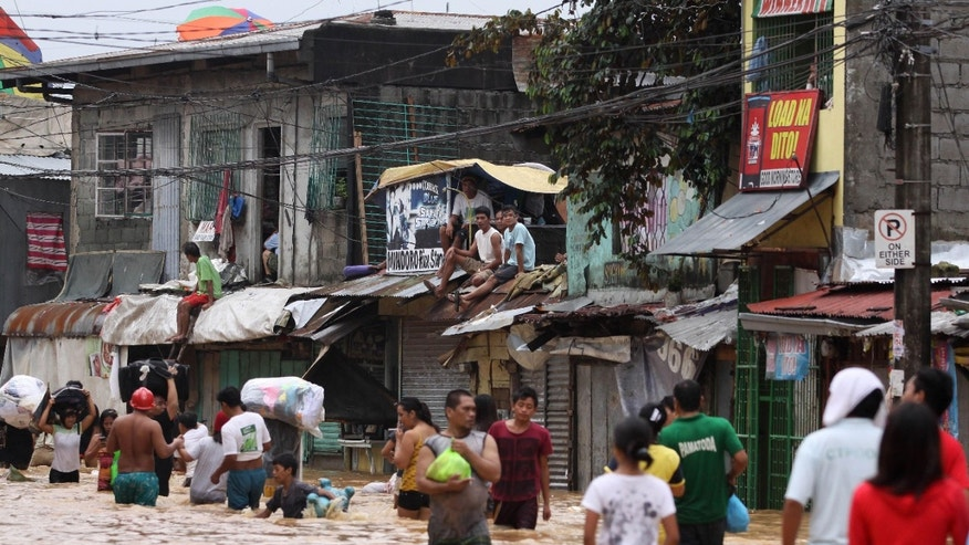 Aug. 9, 2012 - Residents on a rooftop look at others wade along a flooded road in Marikina, east of Manila, Philippines.