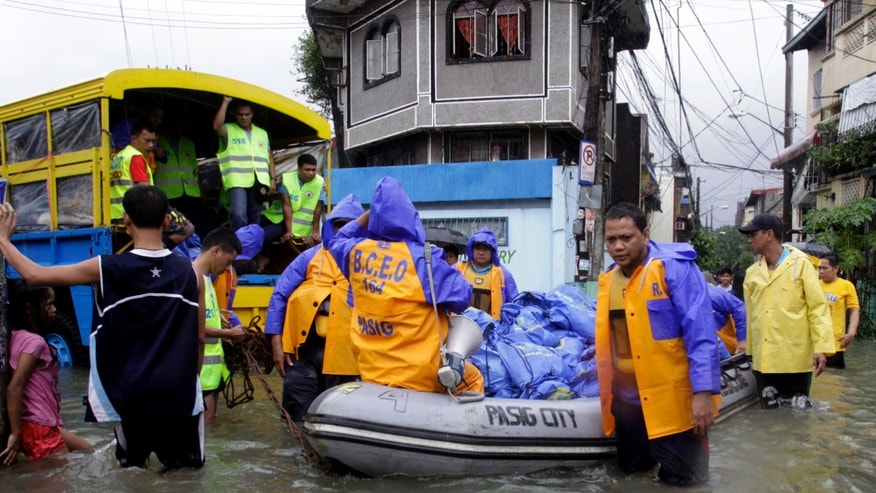 Aug. 9, 2012 Local government employees push a rubber boat loaded with relief goods in suburban Pasig City, east of Manila, Philippines.