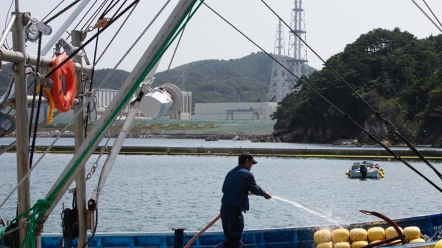 July 31, 2012: A fisherman washes his fishing boat near the Onagawa nuclear power plant, seen at left, in Onagawa, Miyagi prefecture.