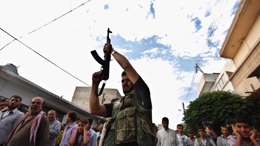 Aug. 9, 2012: A Syrian gunman shoots in the air during the funeral of 29 year-old Free Syrian Army fighter, Husain Al-Ali, who was killed during clashes in Aleppo, in the town of Marea on the outskirts of  Aleppo city, Syria.