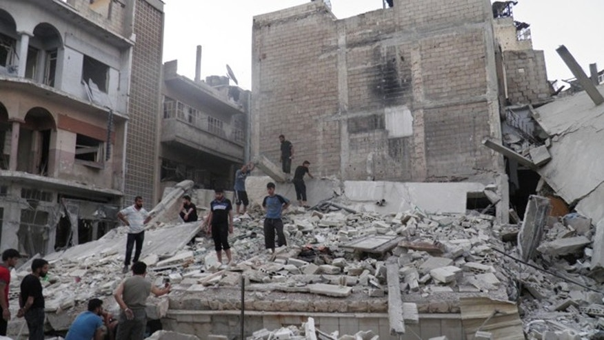 Aug. 11, 2012: This citizen journalism image provided by Shaam News Network SNN purports to show Syrians standing in the rubble of a destroyed building from Syrian forces shelling in Khaldiyeh neighborhood, Homs province, central Syria.