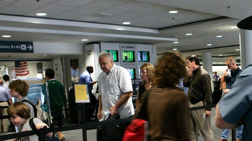 In this Thursday, Aug. 10, 2006 file photo, a Massachusetts state trooper keeps watch over travelers making their way through Logan International Airport in Boston. (AP Photo/Elise Amendola, File)