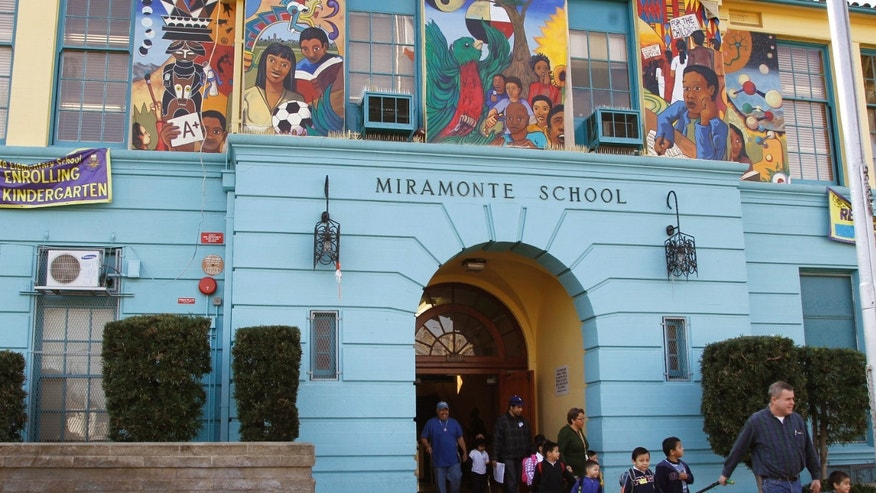 Students are escorted to a waiting bus as they leave Miramonte Elementary school after classes Tuesday, Jan. 31, 2012 in Los Angeles.