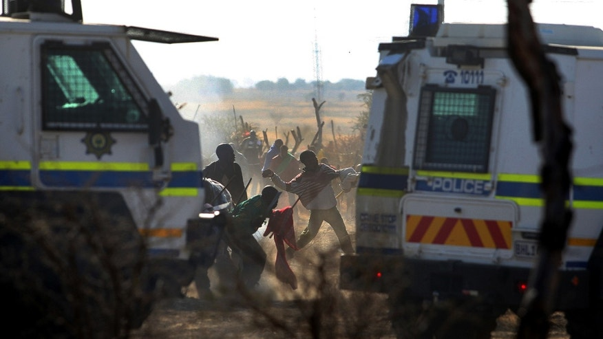 Aug. 16, 2012: Striking mineworkers throw stones as police open fire on striking miners at the Lonmin Platinum Mine near Rustenburg, South Africa.