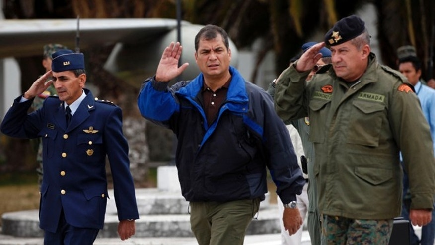 In this photo released by Ecuador's Presidency, Ecuador's President Rafael Correa, center, waves before flying by plane to the Ecuadorean city of Loja at the airport in Quito, Ecuador, Thursday, Aug. 16, 2012. Ecuador would grant asylum to WikiLeaks' founder Julian Assange two months after he took refuge in its London embassy to avoid extradition to Sweden to face questioning for alleged sexual misconduct. (AP Photo/Ecuador's Presidency)