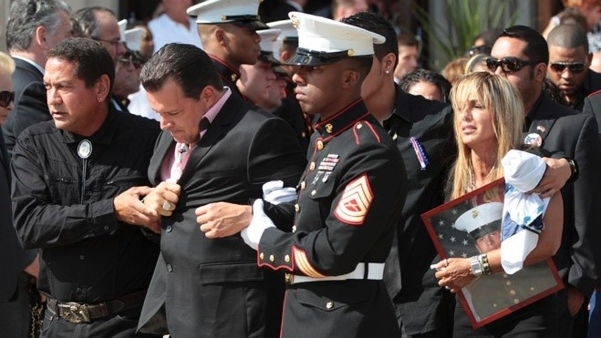 Aug. 18, 2012: Lance Cpl. Greg Buckley Jr.'s father Greg, foreground and mother Marina are escorted from St. Agnes Cathedral after his funeral Mass in Rockville Center, N.Y..