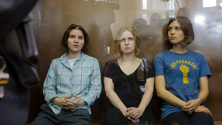 Aug. 17: Feminist punk group Pussy Riot members, Nadezhda Tolokonnikova, right, Maria Alekhina, center, and Yekaterina Samutsevich, sit in a glass cage at a court room in Moscow.
