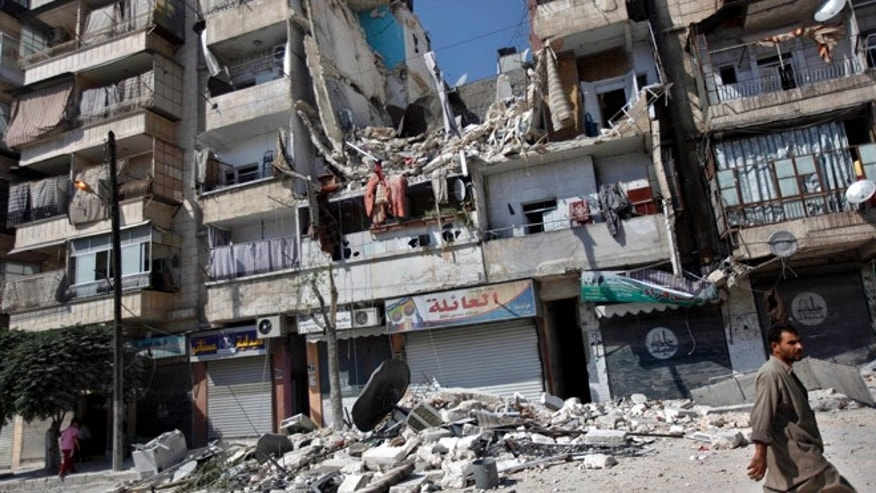 Aug. 17, 2012: A Syrian man walks by a building destroyed in an airstrike in Aleppo city, Syria.