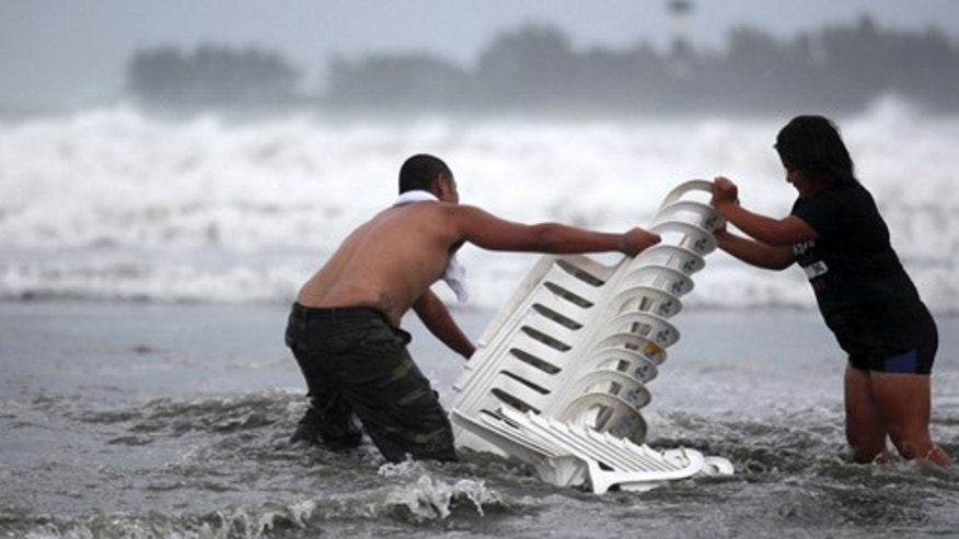 Vendors that were caught unprepared try to recover their chairs after high waves dragged their beach stalls into the sea in Veracruz, Mexico, Thursday Aug. 9, 2012.   Tropical Storm Ernesto headed into Mexico's southern Gulf coast as authorities in the flood-prone region prepared shelters, army troops and rescue personnel for drenching rains. (AP Photo/Felix Marquez)