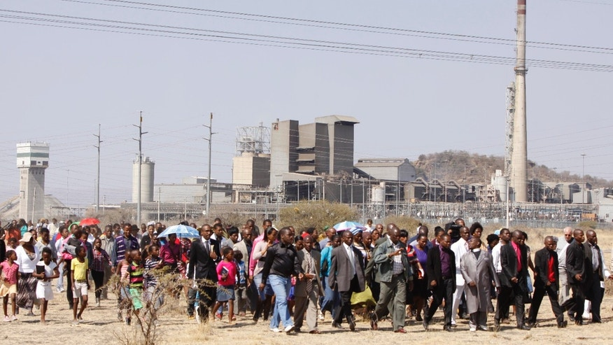 Aug. 19, 2012: A group of churchgoers proceed to the site at the Lonmin platinum mine, background, near Rustenburg, South Africa, for a memorial service for 34 dead striking miners who were shot and killed bt police last Thursday.