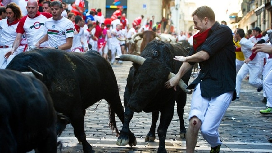 PAMPLONA, SPAIN - JULY 12:  Revelers run with bulls from the Victoriano del Rio ranch along Estafeta street on the sixth day of the San Fermin running-of-the-bulls on July 12, 2012 in Pamplona, Spain. Pamplona's famous Fiesta de San Fermin, which involves the running of the bulls through the historic heart of Pamplona for eight days starting July 7th, was made famous by the 1926 novel of U.S. writer Ernest Hemmingway called 'The Sun Also Rises.'  (Photo by Jasper Juinen/Getty Images)