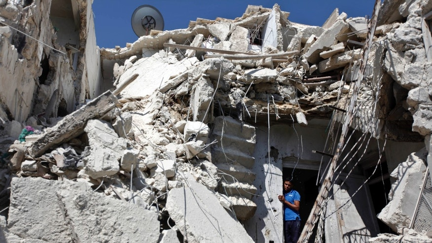 Aug. 19, 2012: A Syrian man looks out of the rubble as rescuers, not shown, look for the bodies of two girls thought to be under the rubble of a building hit by a Syrian government airstrike in Aleppo, Syria.