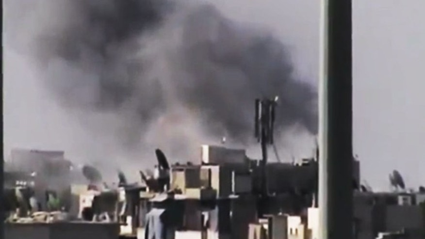 July 31, 2012: This file photo image made from amateur video released by the Ugarit News purports to show black smoke rising from buildings in Aleppo, Syria.