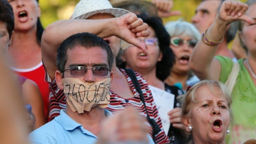 Aug. 21, 2012: Protesters shout anti presidential slogans downtown Bucharest, Romania.