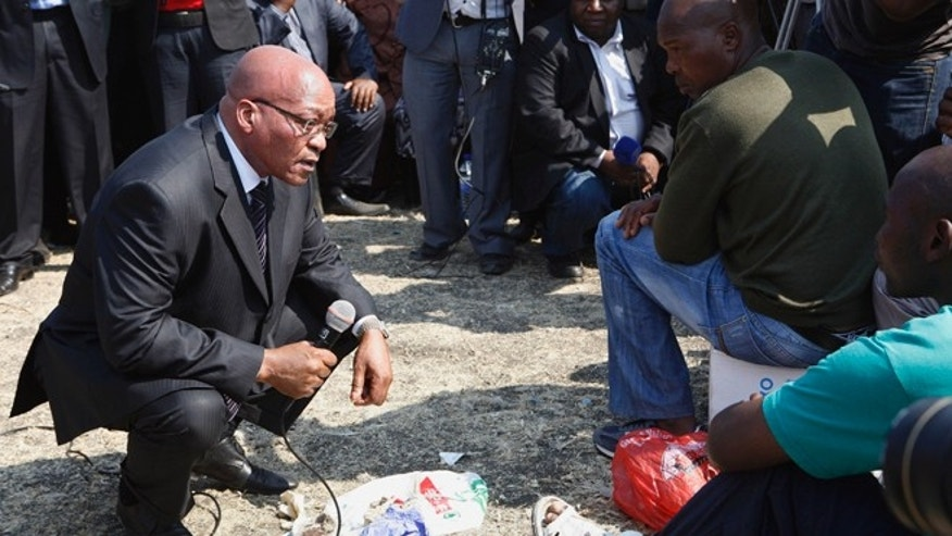 August 22, 2012: South Africa's President Jacob Zuma, left, interacts with striking mine workers at the Lonmin mine near Rustenburg, South Africa.