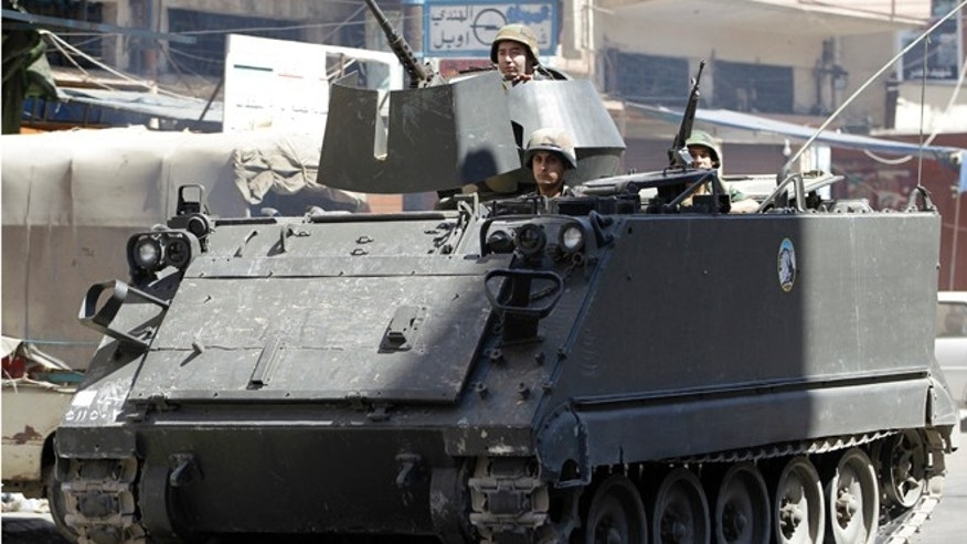 August 22, 2012: Lebanese army soldiers in a armored personnel carrier pass Syria street, which divides areas between supporters and opponents of the Syrian regime, in the northern port city of Tripoli, Lebanon.