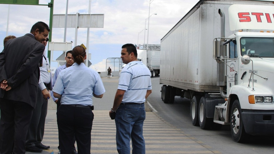 Attorney Emilio de La Rosa, left, and forensics expert Mario Gomez, right, talk to a customs and court officials at the Las Americas Bridge in Juarez, Mexico while doing a reconstruction of the events that lead to the arrest of trucker Jabin Bogan.