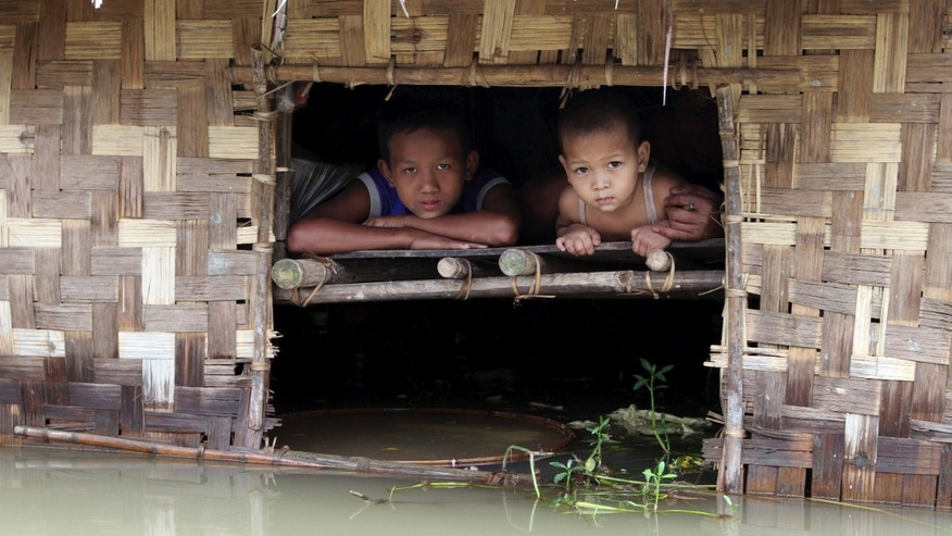 Aug. 17, 2012: Children look out from their house half-submerged in a low-lying area flooded by the Nga-Wun River in Ah-Thouk township, Ayeyarwaddy Delta, about 80 miles southwest of Yangon, Myanmar.