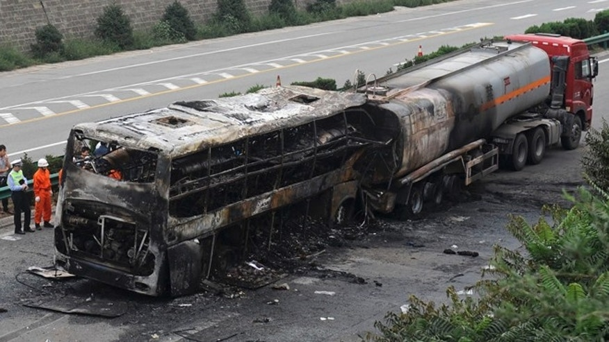 August 26, 2012: Police officer and rescuers inspect the wreckage of a burnt-off bus and a tanker on an expressway in Yan'an in northwest China's Shaanxi province.