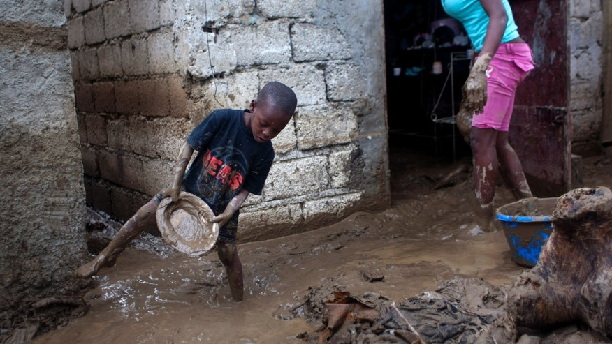 Sunday Aug. 26, 2012 - Winsky Pierre, 5, helps to drain mud from his flooded house after the passing of Tropical Storm Isaac in Port-au-Prince, Haiti.