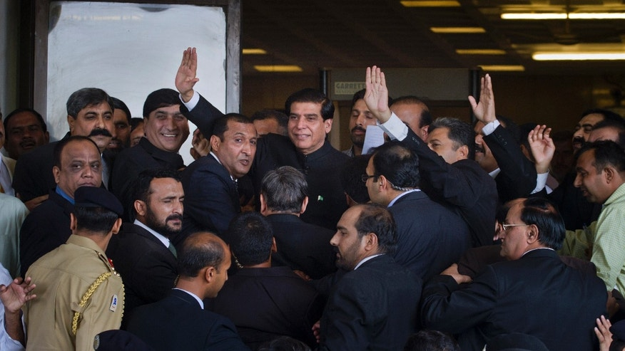 Aug. 27, 2012: Pakistan's Prime Minister Raja Pervaiz Ashraf, center, waves as he is surrounded by security staff upon his arrival at the Supreme Court for a hearing in Islamabad, Pakistan.