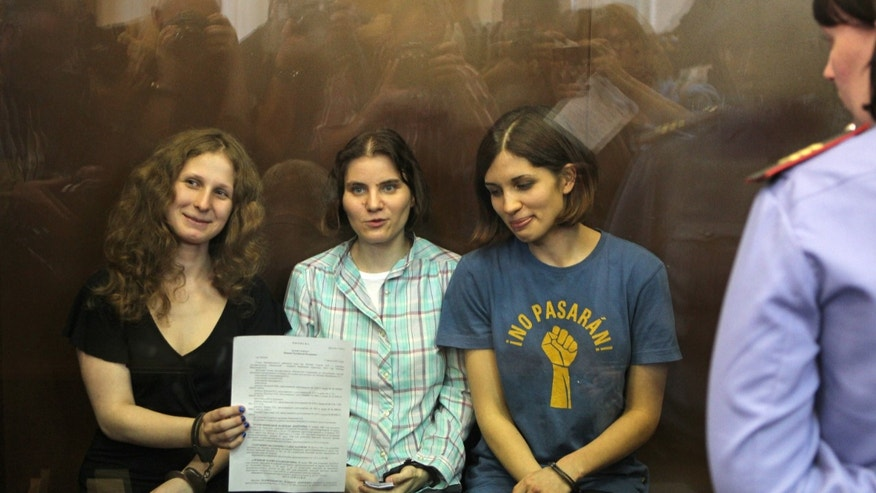 Aug. 17, 2012: Feminist punk group Pussy Riot members, from left, Maria Alekhina, Yekaterina Samutsevich, and Nadezhda Tolokonnikova show the court's verdict as they sit in a glass cage at a court room in Moscow, Russia.