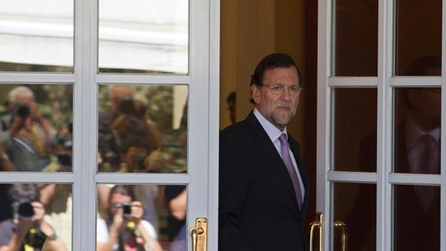 Photographers are seen reflected in a glass door as Spain's Prime Minister Mariano Rajoy steps out to greet   European Council President Herman van Rompuy, unseen at the Moncloa Palace in Madrid Tuesday Aug. 28, 2012.  Rajoy and van Rompuy met for talks on the economic crisis and Spain's battle to avert having to seek a sovereign bailout. (AP Photo/Paul White)