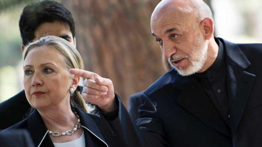 July 7, 2012: U.S. Secretary of State Hillary Rodham Clinton, left, walks with Afghanistan President Hamid Karzai to a news conference at the Presidential Palace in Kabul.