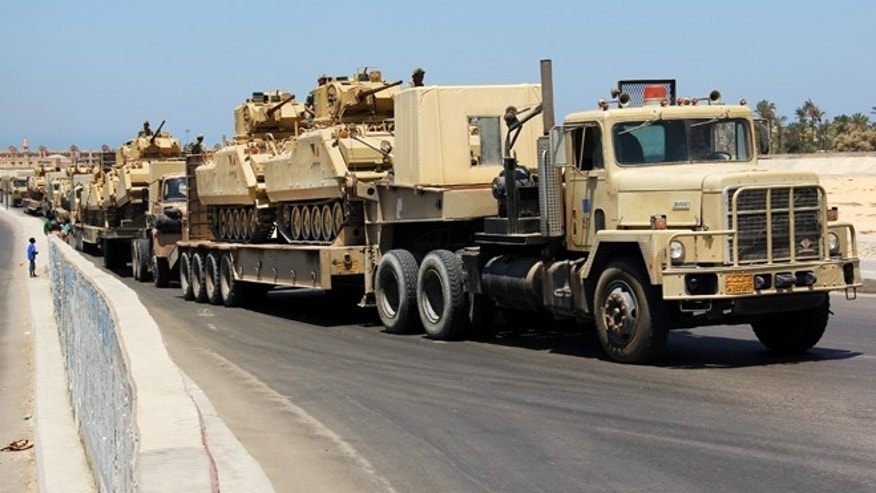 FILE - In this Aug. 9, 2012 file photo, army trucks carry Egyptian military tanks in El Arish, Egypt's northern Sinai Peninsula.