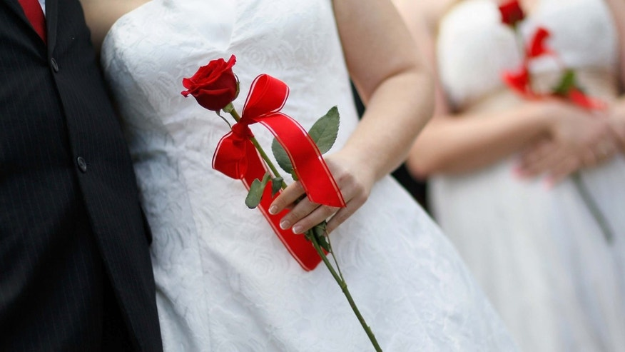 WEST PALM BEACH, FL - FEBRUARY 14:  Brides hold their roses during a group Valentine's day wedding at the National Croquet Center on February 14, 2012 in West Palm Beach, Florida. The group wedding ceremony is put on by the Palm Beach Country Clerk & Comptroller's office and 30 couples to tied the knot. (Photo by Joe Raedle/Getty Images)