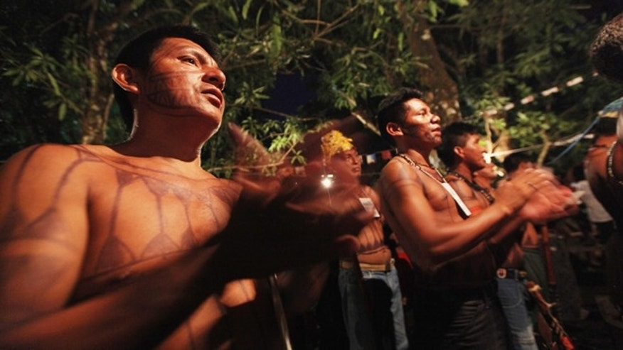 ALTAMIRA, BRAZIL - JUNE 13: Indigenous people from the Kuruaia and Xipaia tribes attend Mass at the start of the Xingu +23 event that gathers resisters of the Belo Monte dam project in the Amazon basin on June 13, 2012 in Santo Antonio, near Altamira, Brazil.  Santo Antonio is adjacent to where the Belo Monte dam complex is under construction and the entire community will be expropriated for the construction. Around 60 families originally lived in Santo Antonio but now only about ten families remain. Xingu +23 is an event running parallel to the United Nations Rio + 20 event and marks 23 years since the first meeting of indigenous peoples opposed to the dam in 1989. Belo Monte will be the world?s third-largest hydroelectric project and will displace up to 20,000 people while diverting the Xingu River and flooding as much as 230 square miles of rainforest. The controversial $16 billion project is one of around 60 hydroelectric projects Brazil has planned in the Amazon to generate electricity for its rapidly expanding economy. The Brazilian Amazon, home to 60 percent of the world?s largest forest and 20 percent of the Earth?s oxygen, remains threatened by the rapid development of the country. The area is currently populated by over 20 million people and is challenged by deforestation, agriculture, mining, a governmental dam building spree, illegal land speculation including the occupation of forest reserves and indigenous land and other issues. Over 100 heads of state and tens of thousands of participants and protesters will descend on Rio de Janeiro, Brazil, later this month for the Rio+20 United Nations Conference on Sustainable Development or ?Earth Summit?. Host Brazil is caught up in its own dilemma between accelerated growth and environmental preservation. (Photo by Mario Tama/Getty Images)