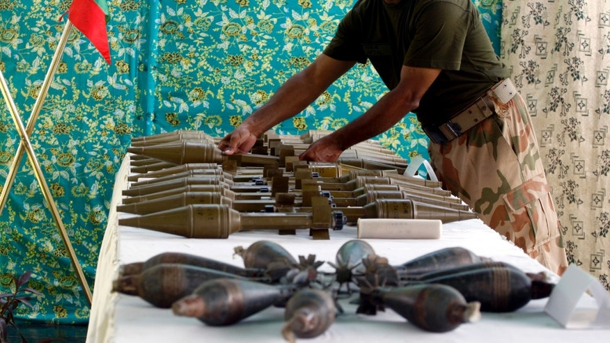 A Pakistani army soldier arranges weapons reportedly recovered from hideouts of militants in tribal areas, as they are displayed in Peshawar, Pakistan on Wednesday, Aug. 29, 2012. (AP Photo/Mohammad Sajjad)