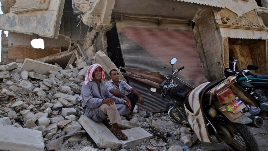 Syrian men rest on the rubble of a shop destroyed form Syrian government forces shelling, while waiting their turn to buy bread from a bakery shop, in the Syrian town of Azaz, on the outskirts of Aleppo, Thursday, Aug. 30, 2012. (AP Photo/Muhammed Muheisen)