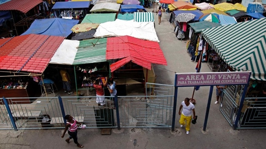 "People walk in an open-air market where the government allows licensed vendors to sell their goods in Havana, Cuba, Friday, Aug. 31, 2012. The entrance sign reads in Spanish ""Sales area for the self-employed."" A jump in import taxes on Monday, Sept. 3 threatens to make life tougher for some of Cuba's new entrepreneurs who the government has been trying to encourage as it cuts a bloated workforce in the socialist economy.  In Cuba, the average monthly wage is about $20. (AP Photo/Franklin Reyes)"