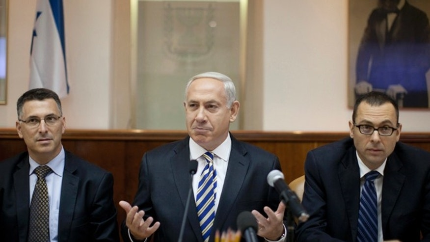 Aug. 26, 2012: Israeli Prime Minister Benjamin Netanyahu, center, heads the weekly cabinet meeting attended by the Israeli Education Minister Gideon Saar, left, and the cabinet secretary, Zvi Houser, right, in the prime minister's office in Jerusalem, Israel.