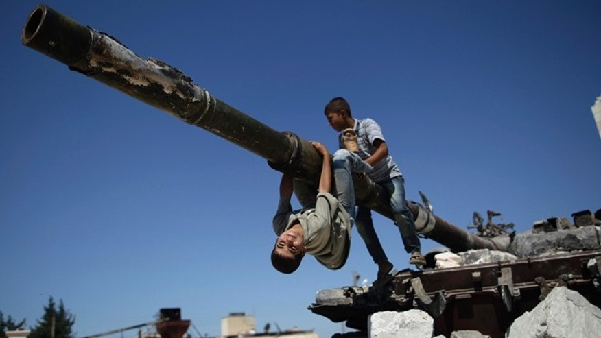 Sept. 2, 2012: A  boy looks back while he and another boy play on a Syrian military tank, destroyed during fighting with the Rebels, in the Syrian town of Azaz.