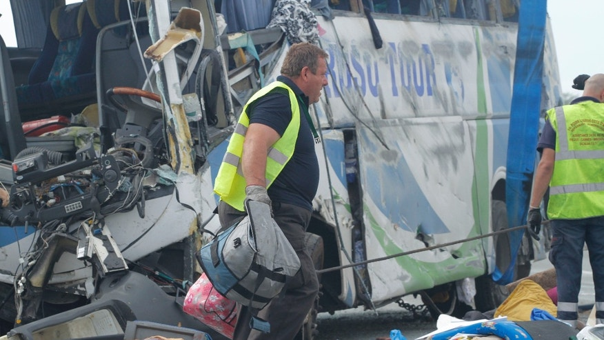 Sept. 2, 2012: A French rescuer carries bags next to the bus which crashed along the A8 highway while carrying about fifty Romanian nationals, near the rest area of Vidauban, southern France.