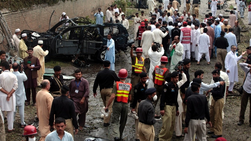 Sept. 3, 2012: Officials and rescue volunteers gather at the bombing site in Peshawar, Pakistan.