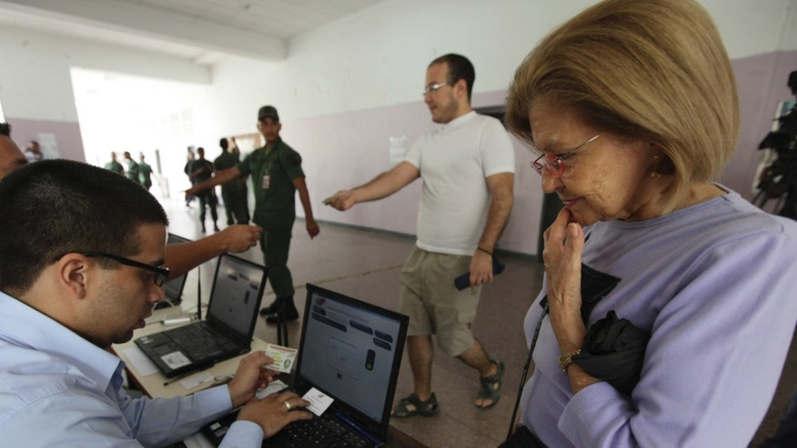 People participate in a mock election to simulate upcoming Oct. 7 presidential election at a polling station in Caracas, Venezuela, Sunday, Aug. 5, 2012. The country's electoral council has long used fingerprint scanners at the entrance to polling places to ensure voter identification. But this year, the readers will be hooked to the electronic voting machines themselves. Citizens must press down a thumb to activate the ballot system. (AP Photo/Fernando Llano)