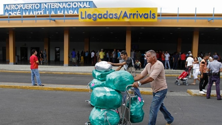 Juan, a Cuban-American man who did not want to give his last name, front, arrives with packages after getting off a flight from the U.S. as his brother, who lives in Cuba, behind, helps him with other packages at the Jose Marti International Airport in Havana, Cuba, Monday, Sept. 3, 2012.  (AP Photo/Franklin Reyes)
