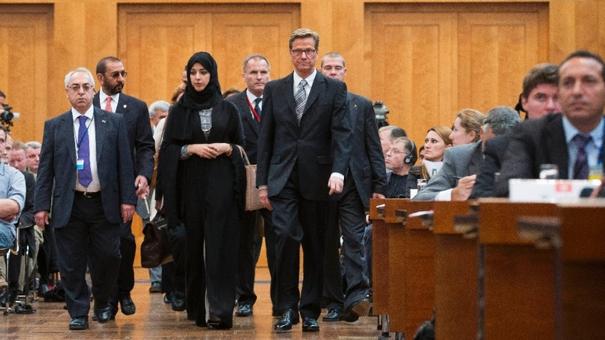 The President of the Syrian National Council Abdulbaset Sieda, Minister of State of the United Arab Emirates Reem al-Hashimi and German Foreign Minister Guido Westerwelle, front from left, arrive at a gathering of Syrian opposition representatives and diplomats hosted at the Germany foreign ministry in Berlin, Tuesday, Sept. 4, 2012. Germany's foreign minister is pressing disparate Syrian opposition groups to unite in preparation for the collapse of the Bashar Assad regime. Berlin hosted a gathering of Syrian opposition representatives and diplomats Tuesday to address how to prevent basic services and infrastructure collapsing, and how to revive the economy, once Assad falls. (AP Photo/Markus Schreiber)