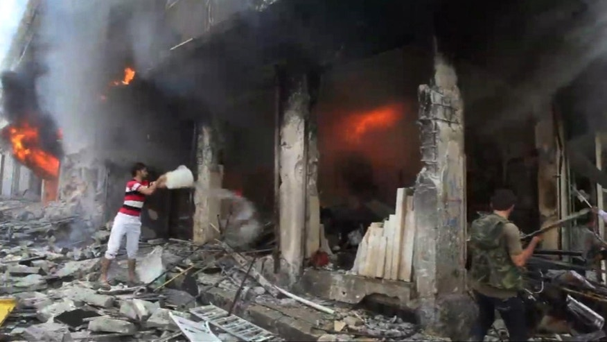 Sept. 4, 2012: This image taken from video filmed by an independent cameraman and made available, shows a Syrian man throwing a bucket of water at a burning building in Myasar neighborhood, Aleppo, Syria. Government jets bombed the residential area of Myasar, reducing many of its buildings to rubble and causing a huge fire.