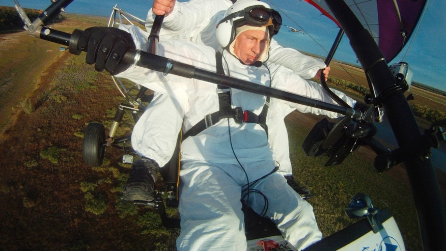 Sept. 5, 2012:  This photo shows Russian President Vladimir Putin, foreground, flies in a motorized hang glider alongside a Siberian white crane, on the Yamal Peninsula, in Russia.