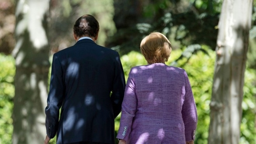Spain's Prime Minister Mariano Rajoy, left, walks with German Chancellor Angela Merkel  prior to a  a news conference at the Moncloa Palace, in Madrid, Thursday, Sept. 6, 2012. (AP Photo)